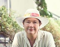 Überzeugte pensionierte Frau an ihrem Land-Häuschen Stockbild