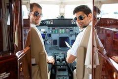 Überzeugte Piloten im Cockpit des Flugzeugs stockfotos