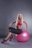 Überzeugte recht blonde Aufstellung mit gymnastischem Ball Stockfoto