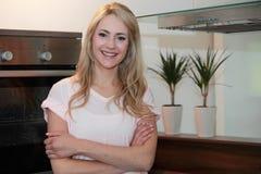 Überzeugte recht blonde Frau zu Hause Lizenzfreie Stockfotografie