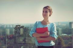 Überzeugte ruhige Geschäftsfrau, die ein rotes Notizbuch mit impor hält Stockfotografie
