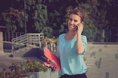 Überzeugte ruhige Geschäftsfrau, die am Telefon spricht und a hält Lizenzfreie Stockbilder