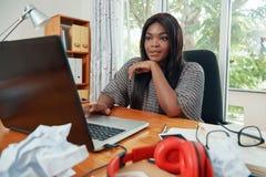 Überzeugte schwarze Geschäftsfrau, die an Laptop arbeitet stockfotos