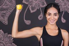Überzeugte Sportlerin, die ihre Muskeln beim Halten eines Handgewichts ausbildet Stockbilder