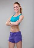 Überzeugte sportliche Frau, die mit den Armen gekreuzt lächelt Lizenzfreie Stockfotos