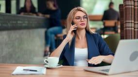 Überzeugte stilvolle Geschäftsfrau, die unter Verwendung des Smartphone sitzt auf Tabelle im Café spricht stock video footage