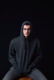 Überzeugte tragende Gläser des jungen Mannes und schwarzer Hoodie, die auf a aufwirft Stockfotos