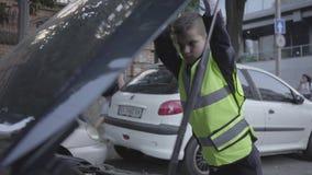Überzeugte tragende Schutzausrüstung des kleinen Jungen, welche die offene Haube eines defekten Autos bereitsteht Junge, der ein  stock video