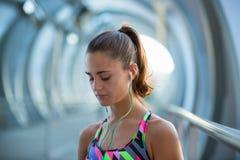 Überzeugte und athletische junge Frau, die vor Übung beim Hören Musik sich konzentriert lizenzfreie stockbilder