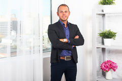 Überzeugte und lächelnde Stellung des hübschen Geschäftsmannes im Büro Lizenzfreie Stockfotografie