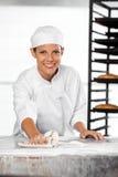 Überzeugte weibliche Bäcker-Cleaning Flour From-Tabelle Stockbild
