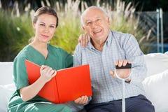 Überzeugte weibliche Krankenschwester And Senior Man mit Buch Stockfoto