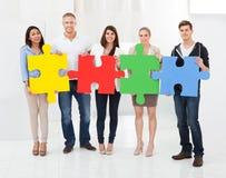 Überzeugte Wirtschaftler, die Puzzlespielstücken sich anschließen Stockfotografie