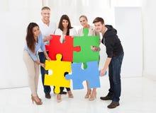 Überzeugte Wirtschaftler, die Puzzlespielstücken sich anschließen Lizenzfreie Stockfotos
