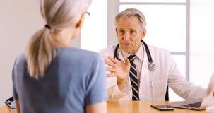 Überzeugter älterer Doktor, der Chirurgieverfahren mit älterem Frauenpatienten bespricht stockbild