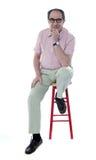 Überzeugter älterer Mann, der auf Schemel stillsteht stockbilder