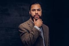 Überzeugter afro-amerikanischer Geschäftsmann in einer braunen klassischen Jacke, denkend an Geschäft beim Halten der Hand auf Ki lizenzfreies stockbild