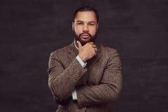 Überzeugter afro-amerikanischer Geschäftsmann in einer braunen klassischen Jacke, denkend an Geschäft beim Halten der Hand auf Ki lizenzfreie stockbilder