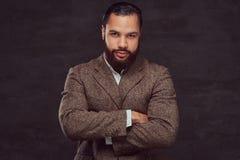 Überzeugter afro-amerikanischer Geschäftsmann in einer braunen klassischen Jacke mit Überfahrt bewaffnet lizenzfreies stockbild