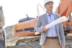 Überzeugter Architekt, der weg schaut, beim Halten an der Baustelle entwirft Lizenzfreie Stockbilder