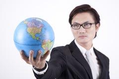 Überzeugter asiatischer Geschäftsmann mit Kugel Stockfotografie
