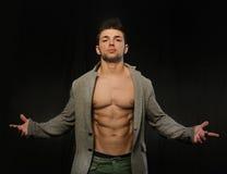 Überzeugter, attraktiver junger Mann mit offener Jacke auf muskulösem Torso Lizenzfreies Stockbild