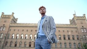 Überzeugter attraktiver Mann mit dem gelockten Ingwerhaar in den Hosen der karierten Hose und in gestreifter Jacke geht am Hinter stock video footage