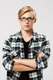Überzeugter blonder hübscher junger Mann in den Gläsern, die zufälliges kariertes Hemd mit den Händen tragen, kreuzte auf dem Kas Stockbild