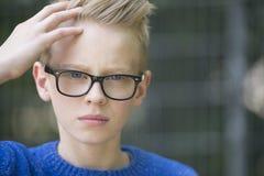 Überzeugter blonder Jugendlicher des Porträts mit Gläsern Lizenzfreies Stockfoto