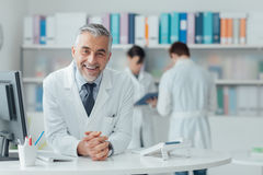 Überzeugter Doktor am Aufnahmeschreibtisch Lizenzfreie Stockbilder