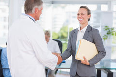 Überzeugter Doktor, der hübsche Geschäftsfrau grüßt Lizenzfreie Stockbilder