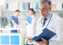Überzeugter Doktor, der Krankenblätter überprüft Stockbild
