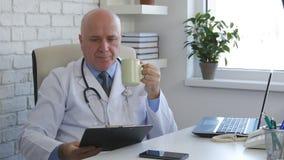 Überzeugter Doktor Enjoy eine Tasse Tee und Lesedokumente stockbilder