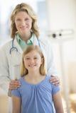 Überzeugter Doktor Standing With Girl in der Klinik Lizenzfreie Stockbilder