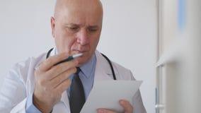 Überzeugter Doktor Writing eine Verordnung für eine ärztliche Behandlung lizenzfreie stockfotografie