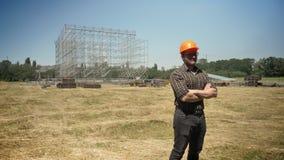 Überzeugter Erbauer, der im Sturzhelm mit den gekreuzten Händen, Metallbau auf Hintergrund, Strohfeld steht stock footage