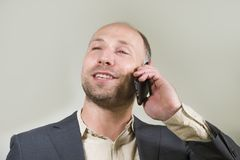 Überzeugter erfolgreicher Geschäftsmann, der am Handy hat Geschäftsgespräch mit dem Mobiltelefonlächeln nett in Unternehmens spri lizenzfreie stockbilder