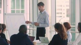 Überzeugter ernster männlicher Geschäftstrainersprecher geben Unternehmens-flipchart Darstellung stock footage