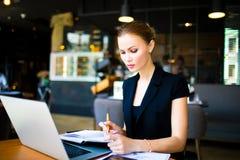 Überzeugter ernster weiblicher Unternehmer, der mit Notizblock und netbook arbeitet stockfotos