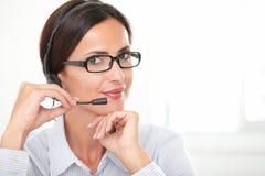 Überzeugter erwachsener Angestellter, der über Kopfhörer spricht stockfotografie