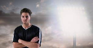 Überzeugter Fußballspieler mit den Armen kreuzte gegen Flutlicht Stockfotos