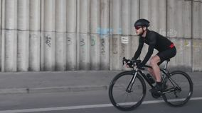 Überzeugter geeigneter fokussierter Radfahrer, der einen tragenden Sturzhelm des Fahrrades, eine schwarze Ausstattung und eine So stock video footage