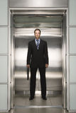Überzeugter Geschäftsmann With Briefcase Standing im Aufzug Stockbild