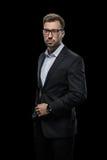 Überzeugter Geschäftsmann, der in den Brillen und in schwarzem Anzug, lokalisiert auf Schwarzem aufwirft Lizenzfreie Stockfotografie
