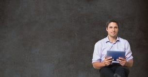 Überzeugter Geschäftsmann, der digitale Tablette beim Sitzen gegen Tafel hält Stockbild