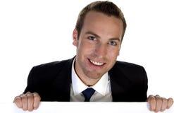 Überzeugter Geschäftsmann, der einen weißen Vorstand anhält Stockbilder