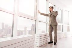 Überzeugter Geschäftsmann, der am Handy spricht Lizenzfreie Stockbilder