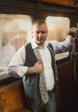 Überzeugter Geschäftsmann, der im Retro- Zug aufwirft Stockfotografie