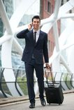 Überzeugter Geschäftsmann, der mit Telefon und Tasche reist Lizenzfreies Stockfoto