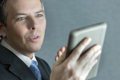 Überzeugter Geschäftsmann, der Tablet Computer gestikuliert Lizenzfreie Stockfotos